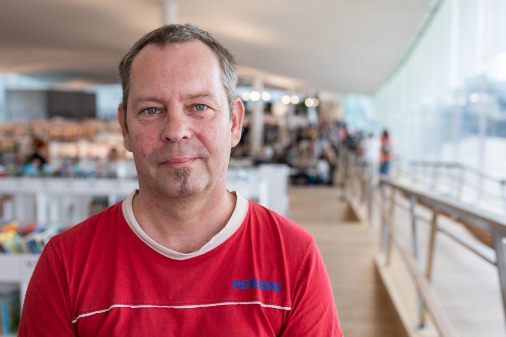Petri hymyilee vienosti kameralle. Taustalla Helsingin kaupunginkirjasto Oodin kirjastokerros.