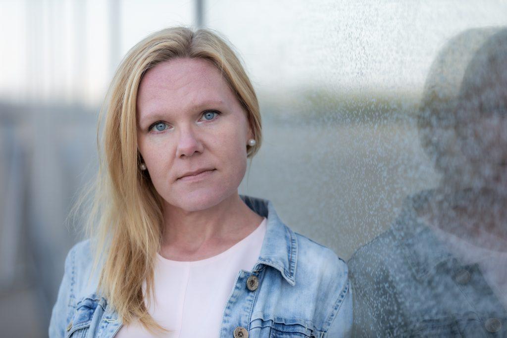 Elina Pekkarinen katsoo totisena kameraan lasiseinään nojaten.