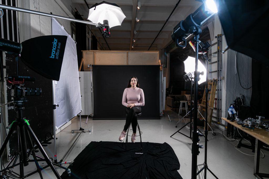Linda-Maria Roine istuu valokuvausstudiossa lamppujen keskellä ja katsoo kameraan.