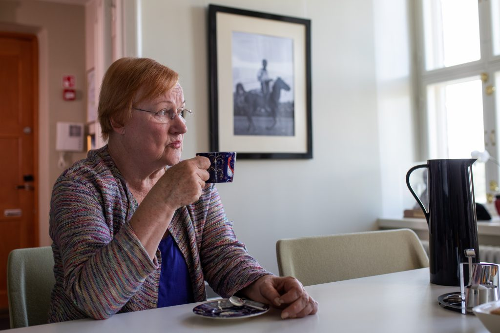 Tarja Halonen istuu työpöytänsä ääressä ja juo kahvia.