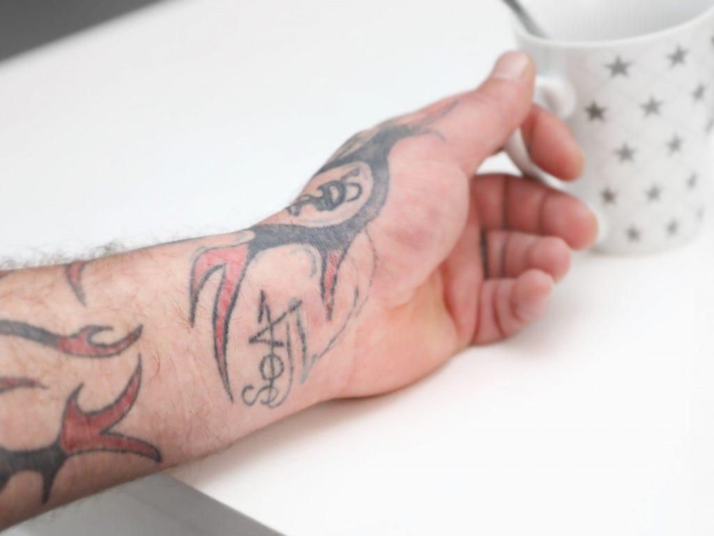 Tatuoitu käsi pitää kiinni kahvikupista.