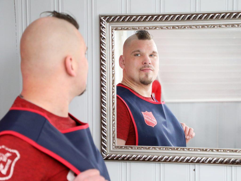 Mies katsoo Pelastusarmeijan liivissä itseään peilistä silmiin, ilme on rauhallinen.