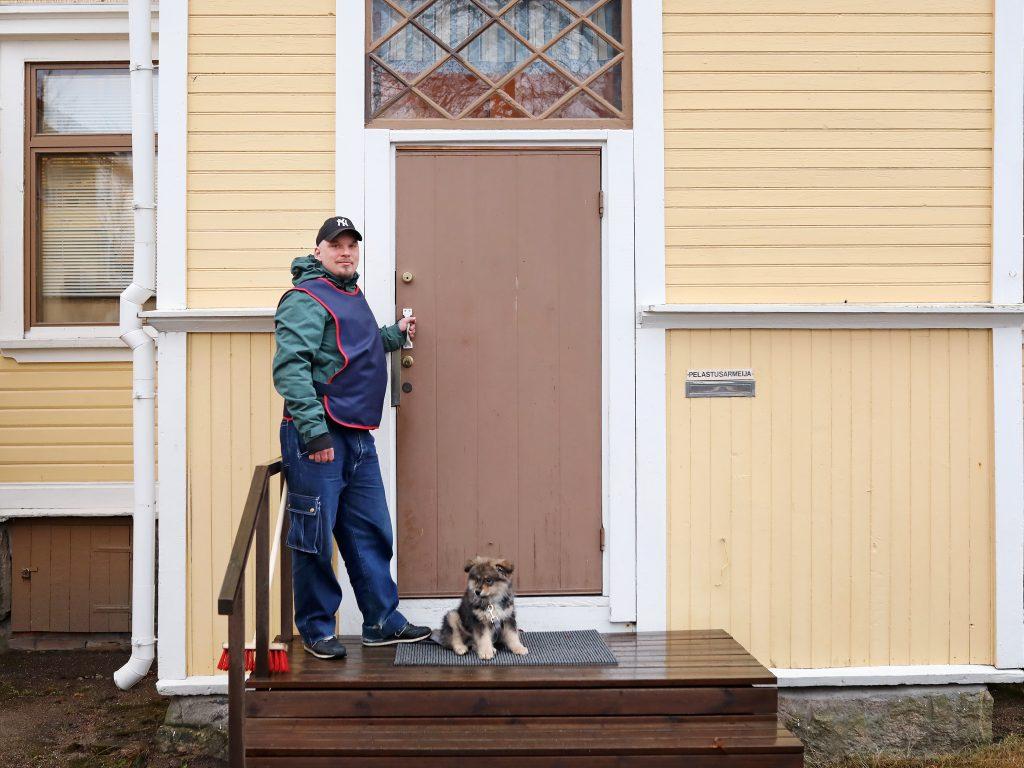 Mies seisoo Pelastusarmeijan liivissä puutalon ulkopuolella, jaloissa pieni koiranpentu.