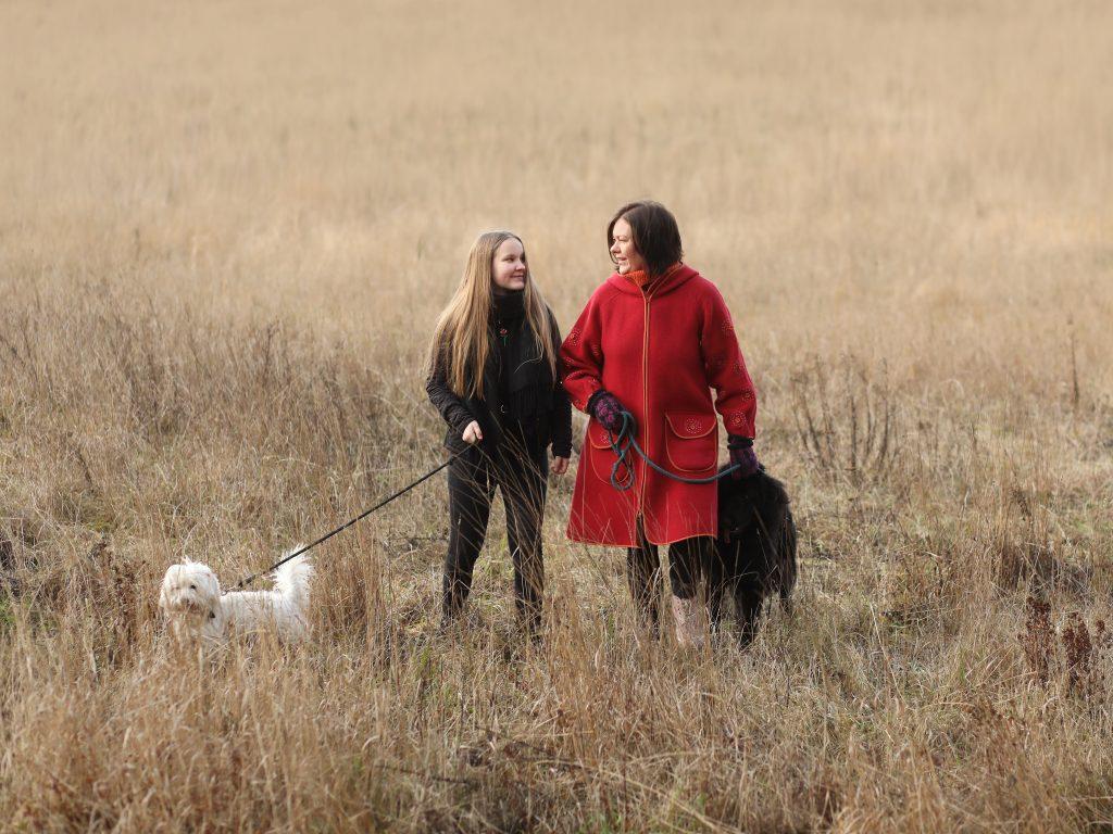 Tytär ja äiti seisovat pellolla kahden koiran kanssa ja katsovat hymyillen toisiaan.